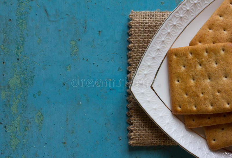 Cookies crackers in a white saucer on a blue background stock photo