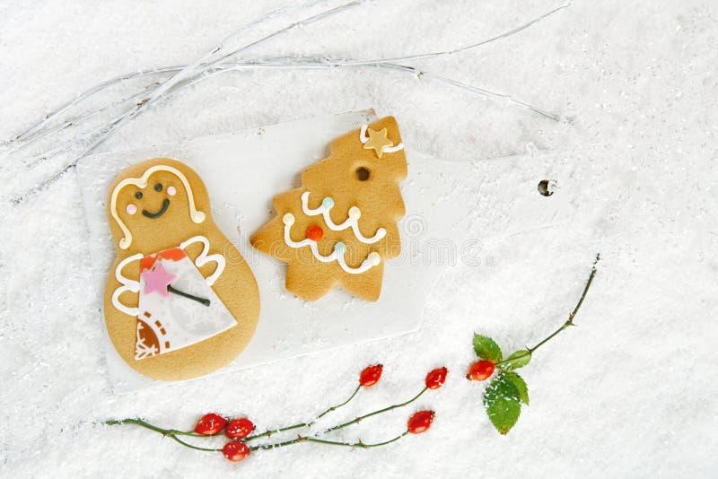 Cookies da árvore e da menina do pão-de-espécie no backgr branco da madeira e da neve fotos de stock royalty free