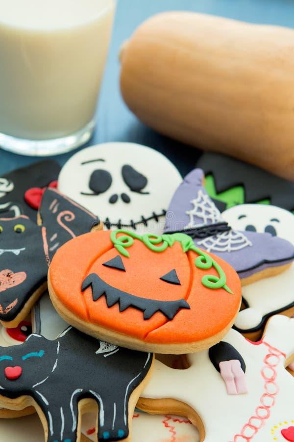 Cookies de Dia das Bruxas com formas diferentes e leite de vidro fotografia de stock