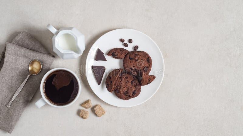 Cookies de farinha de aveia com cacau e chocolate em uma placa branca, na xícara de café e em um jarro de leite imagem de stock royalty free