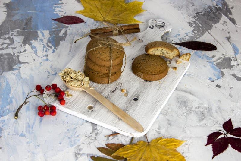 Cookies de farinha de aveia com chocolate e chá no fundo de uma tabela do granito e de uma parede branca com canela e folhas de o imagem de stock royalty free