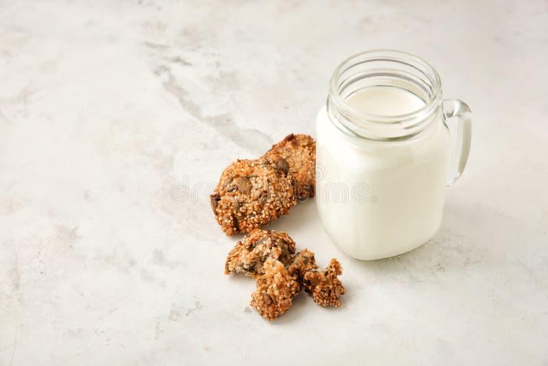 Cookies de farinha de aveia e frasco de pedreiro deliciosos com leite no fundo claro foto de stock royalty free