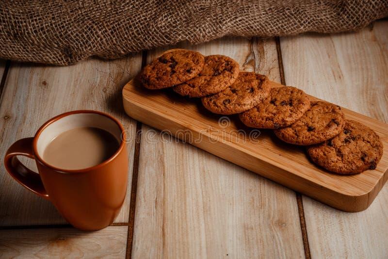 Cookies de farinha de aveia em uma placa de madeira com uma xícara de café com leite O conceito do alimento natural e delicioso imagens de stock