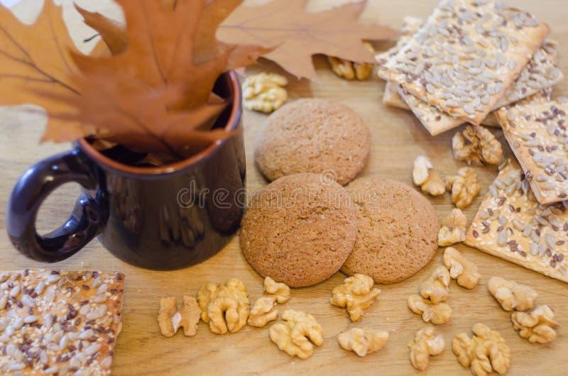Cookies de farinha de aveia, biscoitos do cereal, nozes e copo com folhas imagem de stock