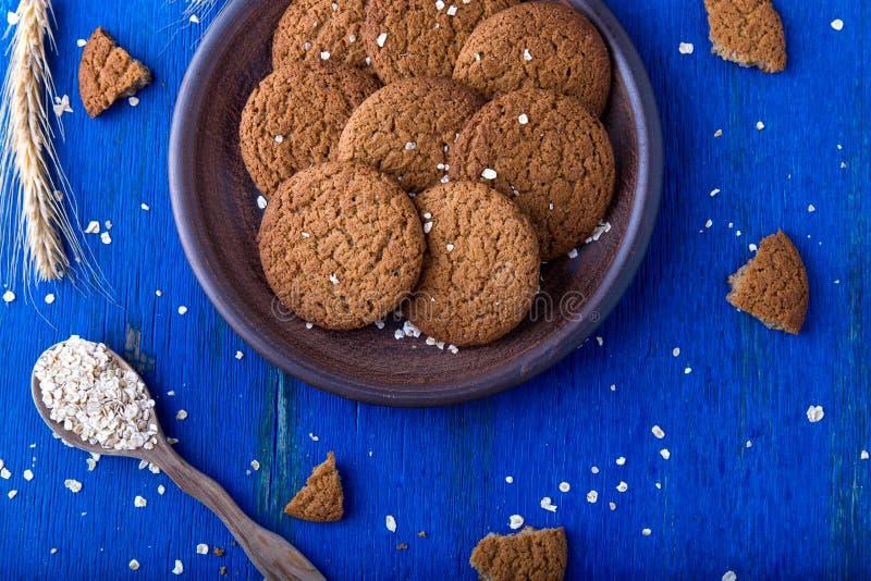 Cookies de farinha de aveia na placa marrom no fundo azul Estilo rústico Vista superior imagem de stock royalty free