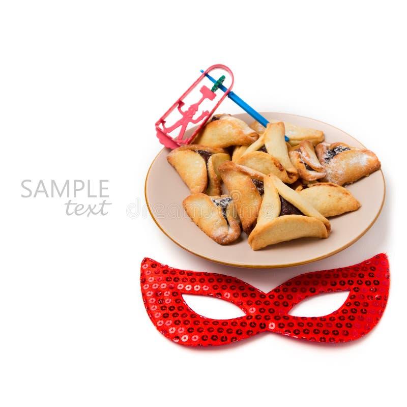 Cookies de Hamantaschen na placa e máscara do carnaval no fundo branco imagem de stock royalty free