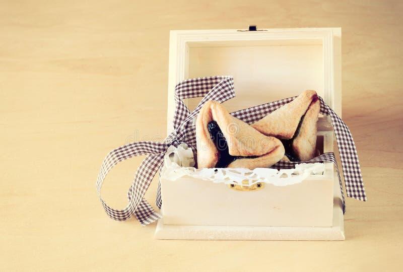Cookies de Hamantaschen ou orelhas dos hamans para a celebração de Purim na caixa de madeira. efeito do vintage. imagens de stock
