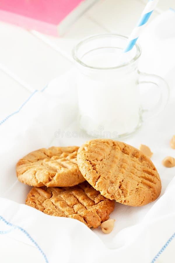 Cookies de manteiga caseiros deliciosas do amendoim com a caneca de leite fotos de stock