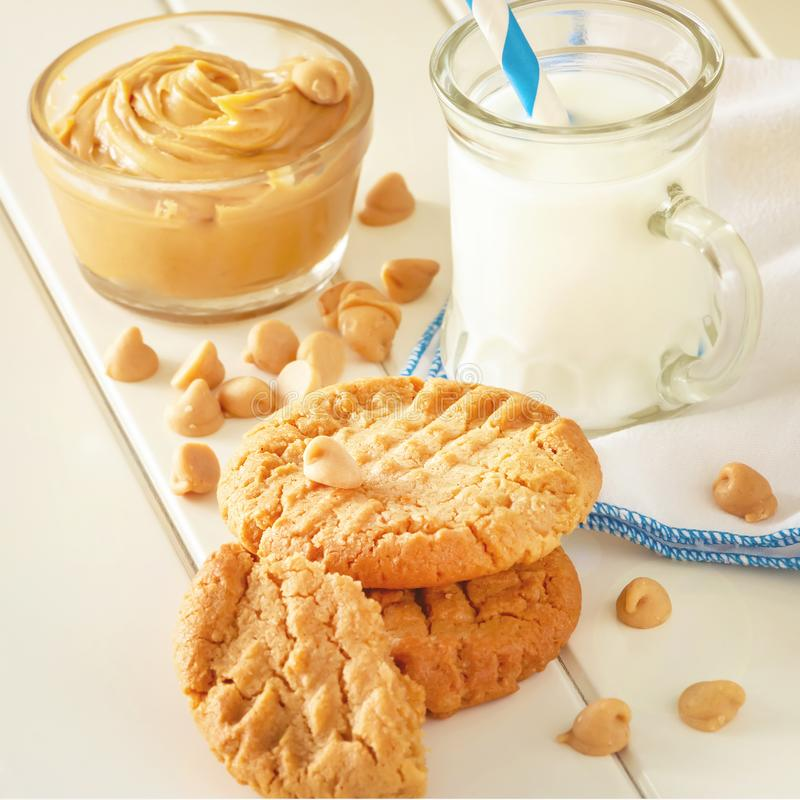 Cookies de manteiga caseiros deliciosas do amendoim com a caneca de leite Fundo de madeira branco Imagem quadrada Foto tonificada imagem de stock royalty free