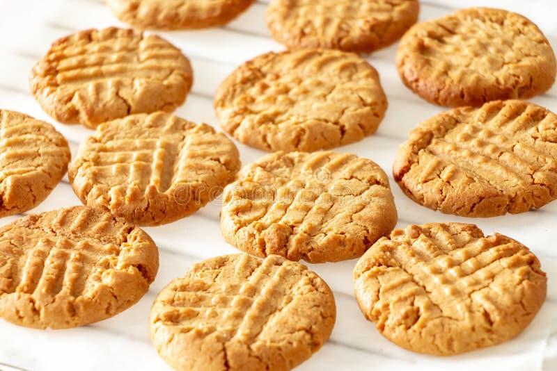 Cookies de manteiga caseiros deliciosas do amendoim na cremalheira refrigerando Fundo de madeira branco Conceito saudável do peti imagem de stock royalty free