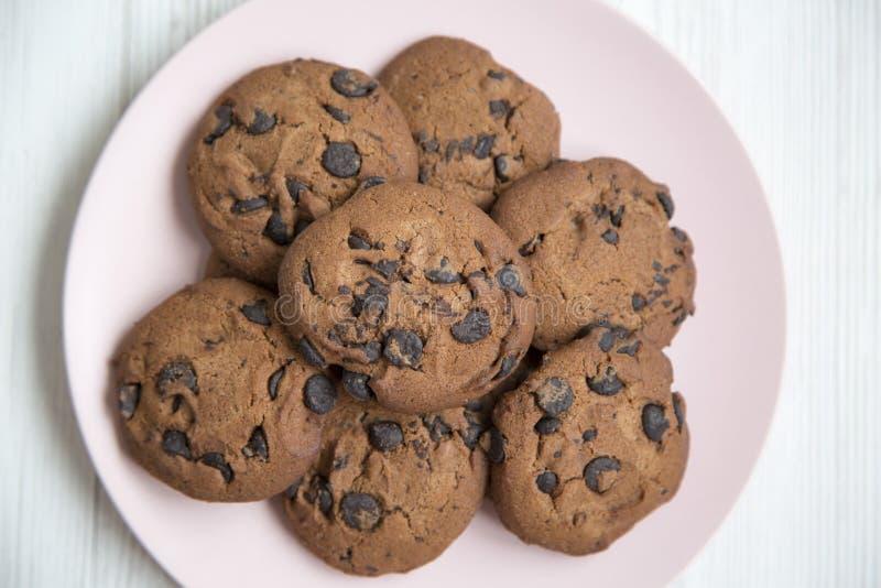 Cookies deliciosas do chocolate em uma placa cor-de-rosa em uma tabela de madeira branca, vista superior De cima de imagem de stock royalty free