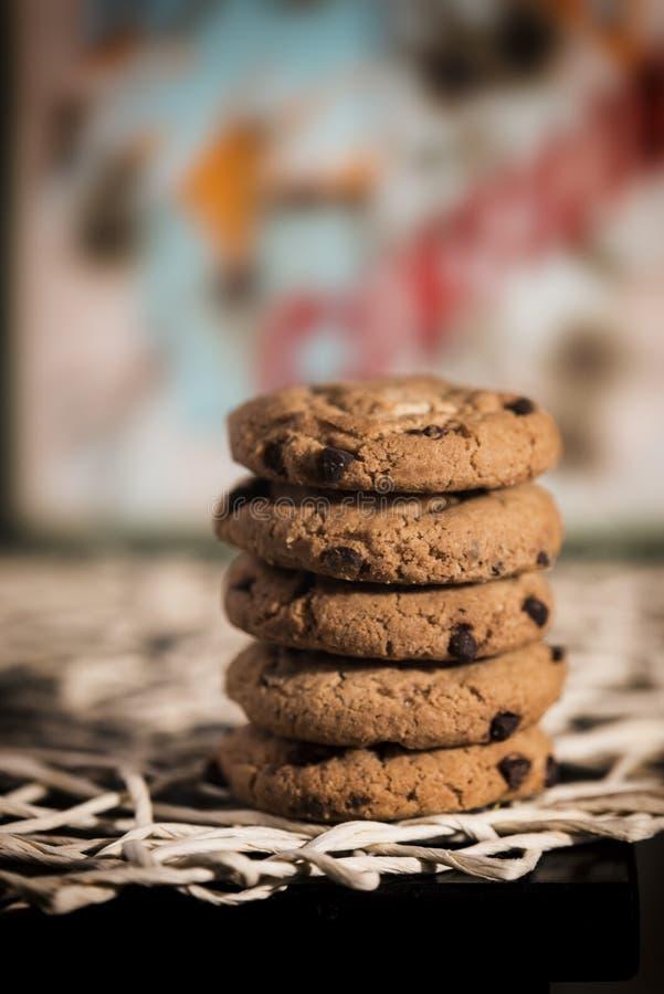 Cookies do chocolate em pe?as centrais, no fundo colorido e no bokeh fotos de stock royalty free