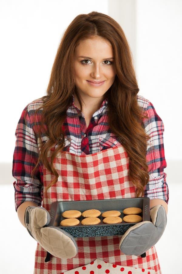 Cookies do cozimento da mulher na cozinha imagens de stock royalty free