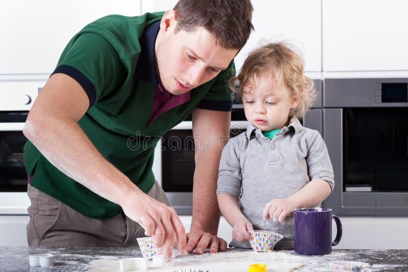 Cookies do cozimento do pai com filho fotografia de stock royalty free