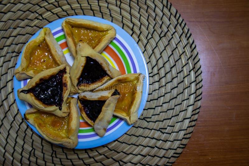 Cookies do doce do mirtilo e do abric? de Hamantash Purim na placa colorida com fundo de madeira da tabela foto de stock royalty free