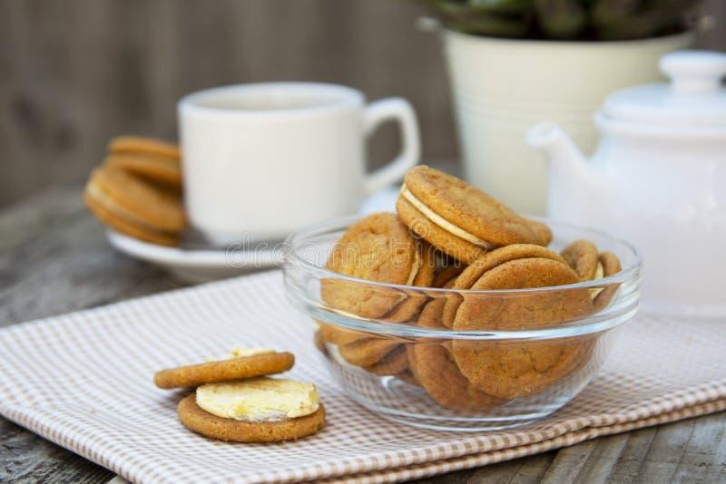 Cookies do gengibre com creme, biscoito para o chá do café, na tabela de madeira Petisco saudável doce do alimento com café, copo fotos de stock royalty free