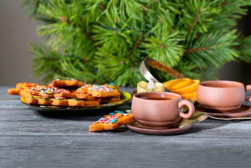 Cookies do gengibre do Natal perto da árvore do ano novo em uma tabela de madeira imagem de stock royalty free