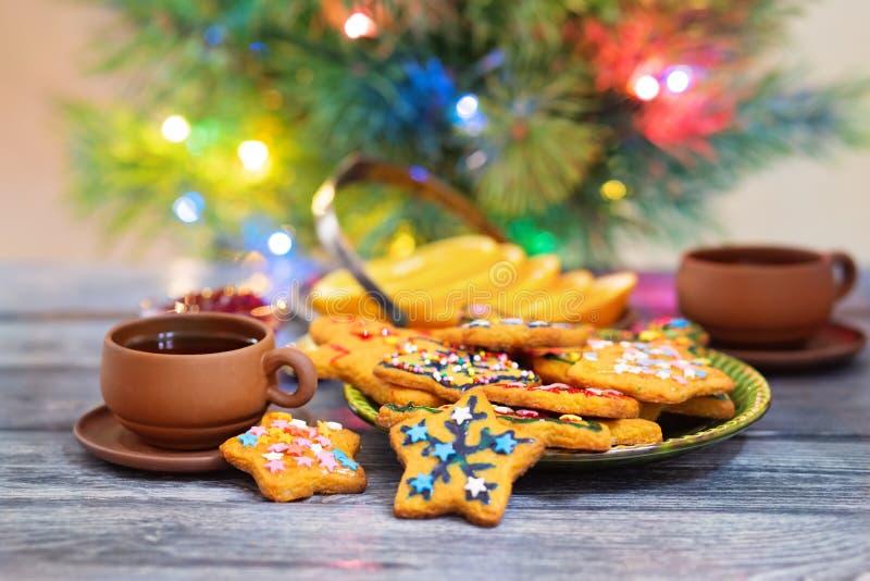 Cookies do gengibre do Natal perto da árvore do ano novo em uma tabela de madeira fotografia de stock royalty free