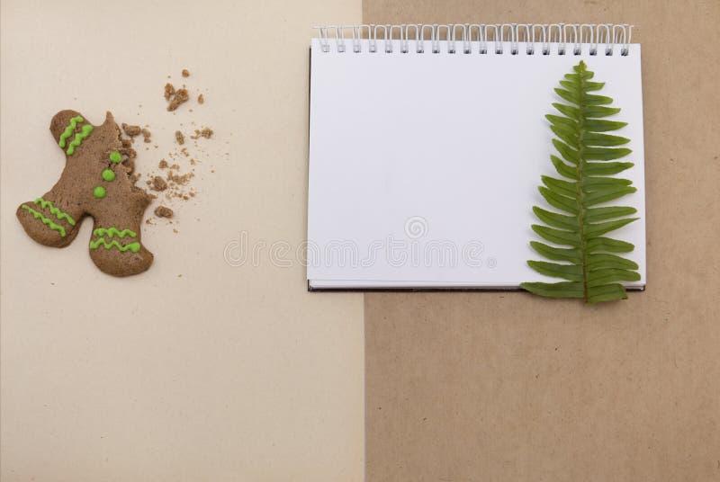 Cookies do pão do gengibre no fundo do papel do ofício Bloco de notas vazio com a folha da samambaia Modelo simples do Natal Vist foto de stock royalty free