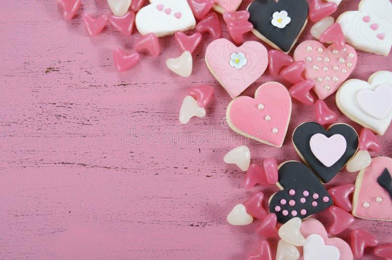 Cookies do rosa da forma do coração, as brancas e as pretas e doces românticos fotografia de stock