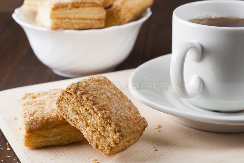 Cookies do sopro em uma bandeja de madeira com um copo do chá foto de stock