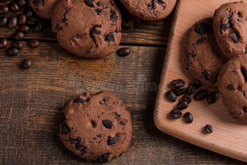 Cookies doces saborosos com chocolate e grões do café em uma tabela de madeira marrom Vista de acima imagens de stock royalty free