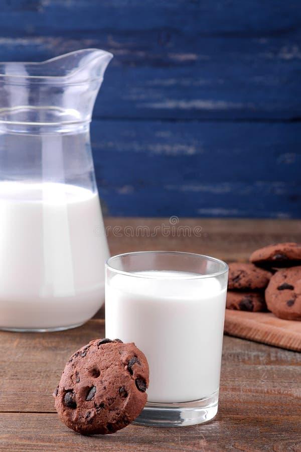 Cookies doces saborosos com chocolate e leite em uma tabela de madeira marrom e em um fundo azul foto de stock