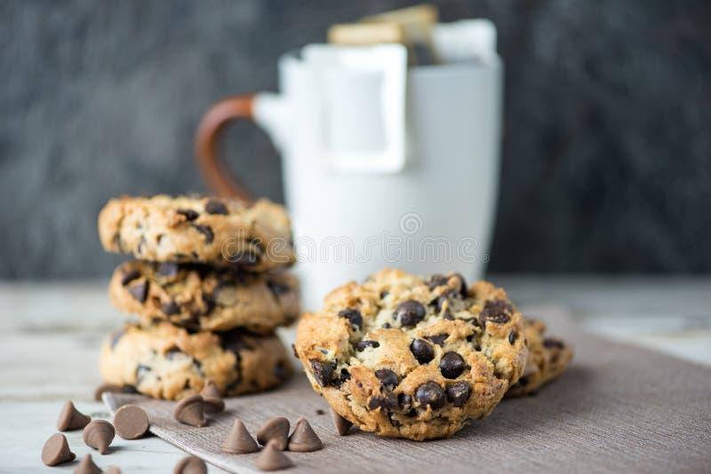 Cookies dos pedaços de chocolate com o copo do café do filtro no backgro do borrão fotos de stock royalty free