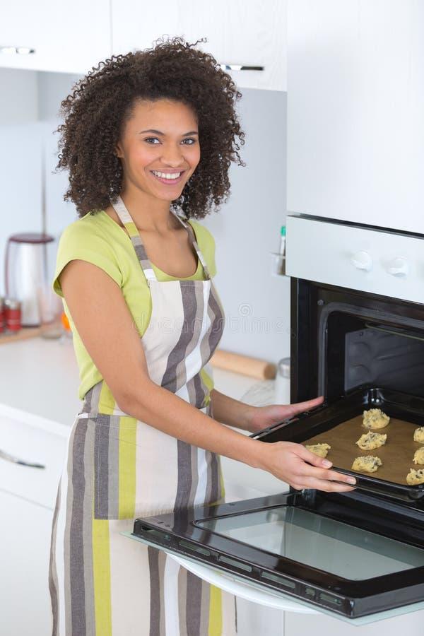 Cookies dos pedaços de chocolate do cozimento da jovem mulher na cozinha fotografia de stock royalty free