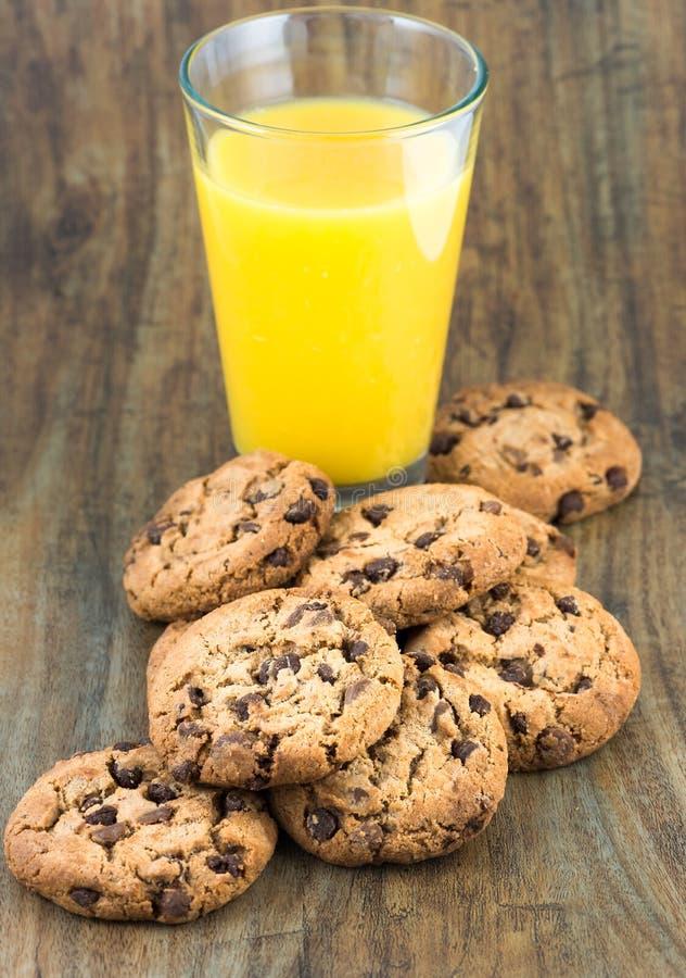 Cookies dos pedaços de chocolate e vidro do suco de laranja fotografia de stock