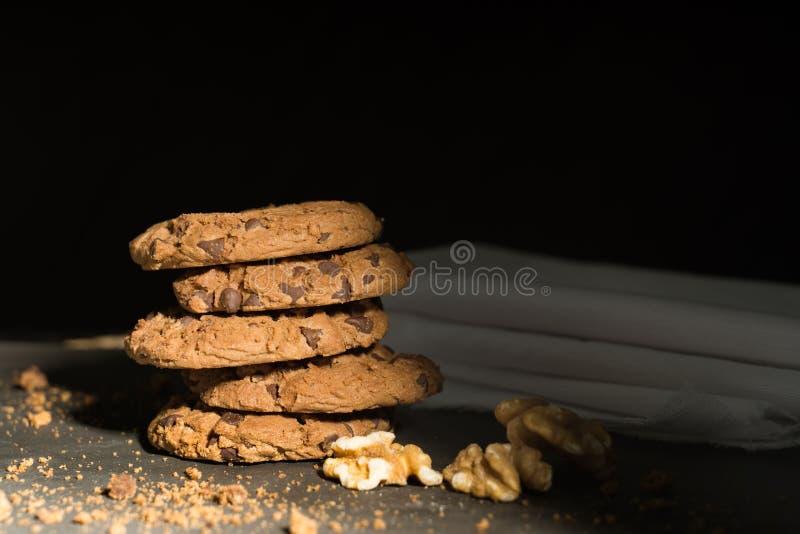 Cookies dos pedaços de chocolate empilhadas acima em uma placa na luminosidade reduzida, seleção do ponto do AF foto de stock