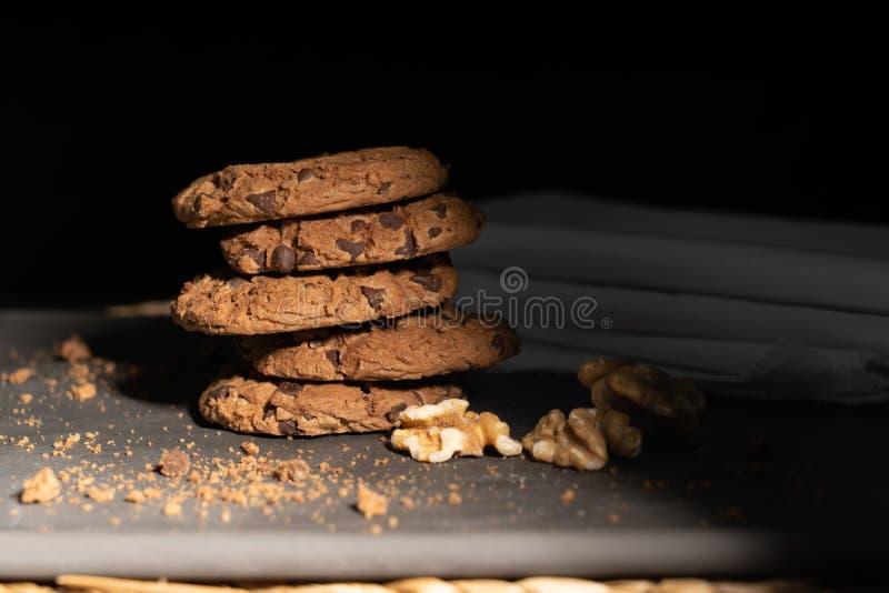 Cookies dos pedaços de chocolate empilhadas acima em uma placa na luminosidade reduzida, seleção do ponto do AF fotografia de stock