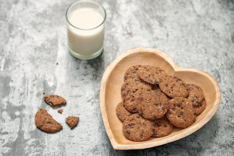 Cookies dos pedaços de chocolate na placa da coração-forma no backgr de pedra cinzento imagens de stock royalty free