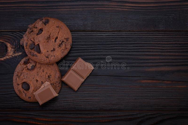 Cookies dos pedaços de chocolate na tabela de madeira velha escura com espaço da cópia foto de stock