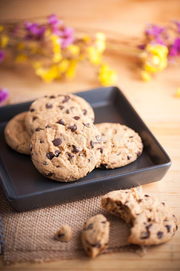 Cookies dos pedaços de chocolate no prato cerâmico preto foto de stock