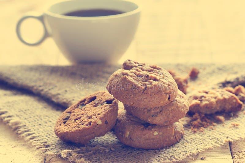 Cookies dos pedaços de chocolate no saco na tabela de madeira, cor do vintage foto de stock