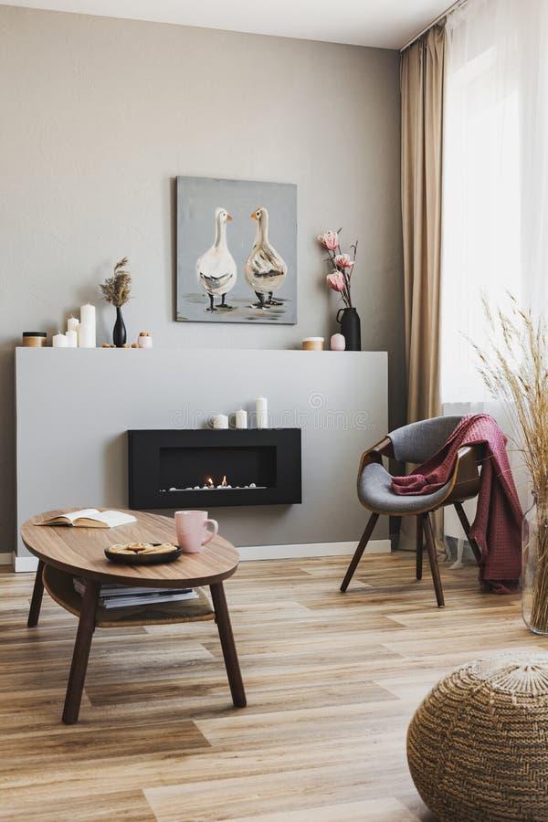 Cookies e caneca cor-de-rosa sobre a mesa de café de madeira no interior cinzento da sala de estar com uma lareira ecológica e um foto de stock