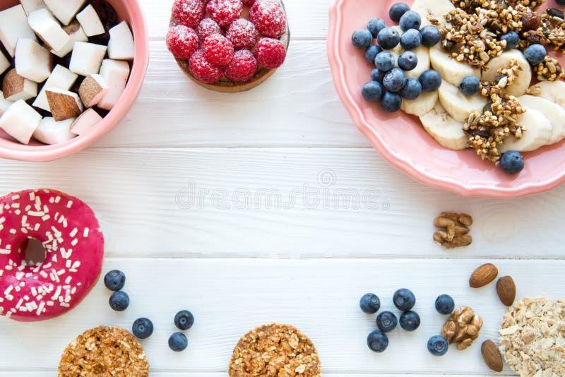 Cookies e granola crocante saudável, partes da banana e do coco, filhós cor-de-rosa e galdéria de framboesa na tabela de madeira  foto de stock