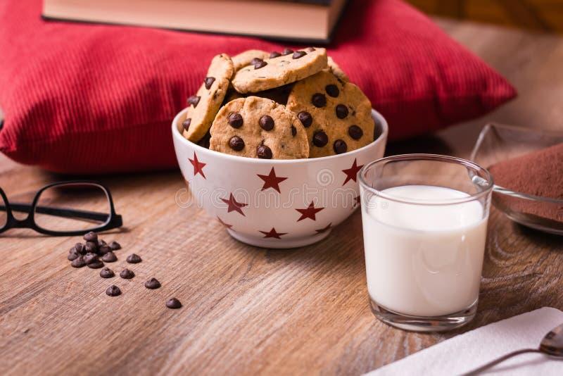 Cookies e leite dos pedaços de chocolate no fundo de madeira imagens de stock