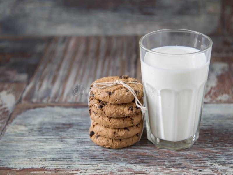 Cookies e vidro do leite no fundo de madeira rústico imagem de stock
