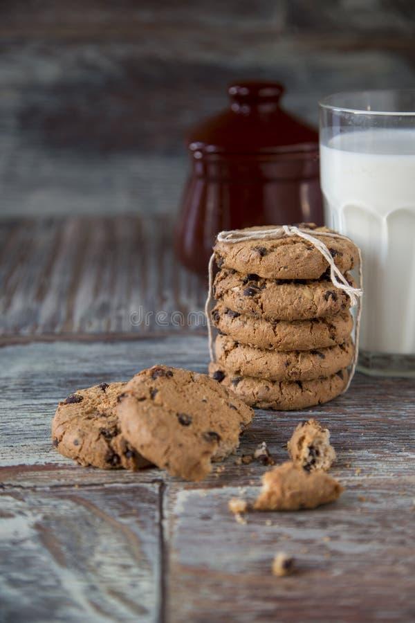 Cookies e vidro do leite no fundo de madeira rústico imagem de stock royalty free