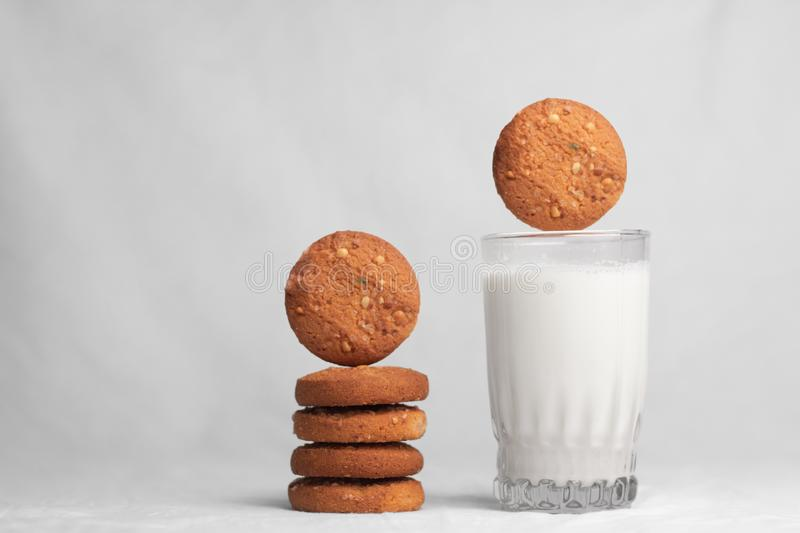 Cookies falling into glass of milk stock photos