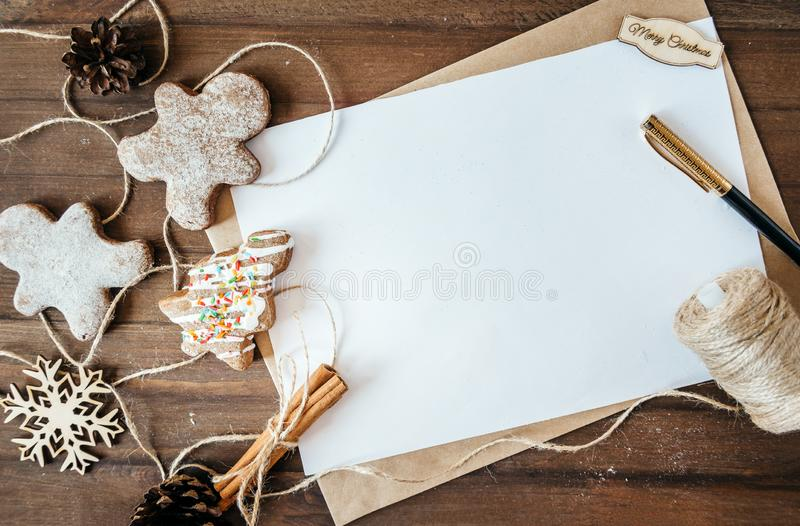 Cookies in the form of Christmas trees, gingerbread man on a brown background, a white sheet in the handle,. Cookies in the form of Christmas trees, gingerbread royalty free stock images