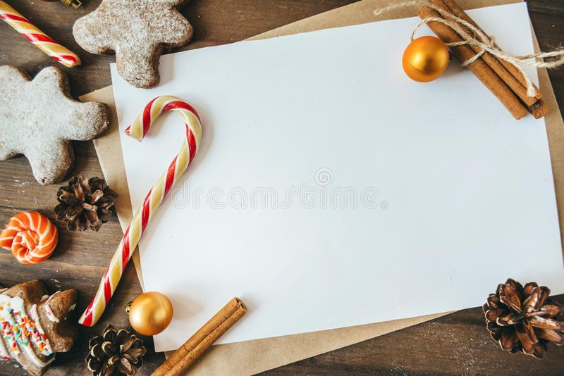 Cookies in the form of Christmas trees, gingerbread man on a brown background, white sheet in the handle,  place for the inscri. Cookies in the form of Christmas royalty free stock photos