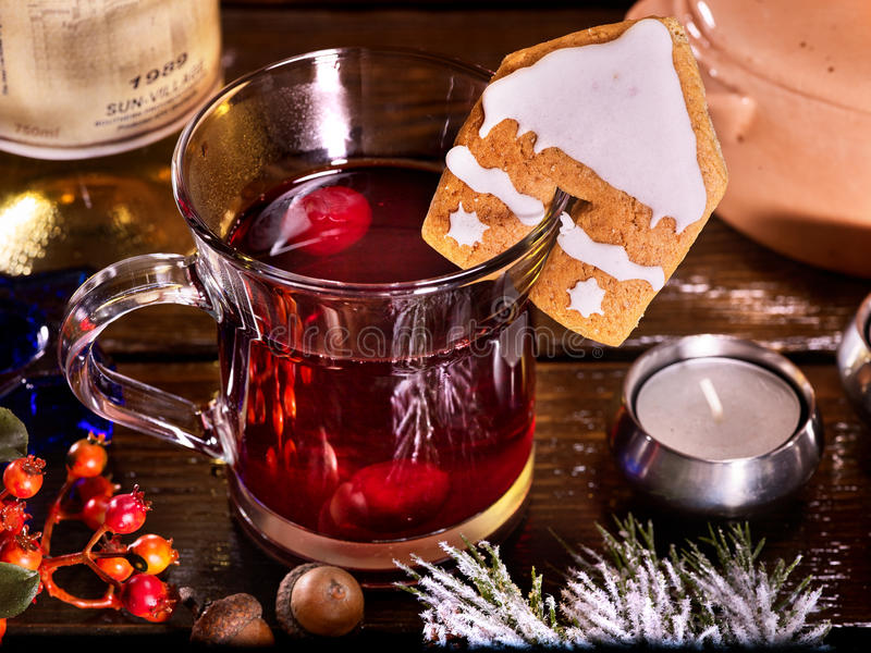 Cookies form of house decorated with glass mug hot drink. Christmas cookies in form of house is decorated with Christmas glass mug with hot winter drink stock photo