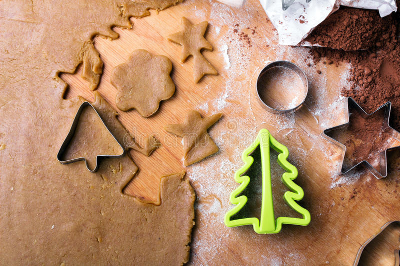 Cookies forms and gingerbread dough on wooden pastry board. Copy space stock images