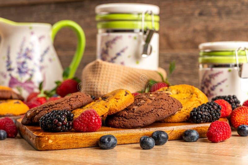 Cookies, framboesas e amoras-pretas na placa de madeira fotos de stock royalty free