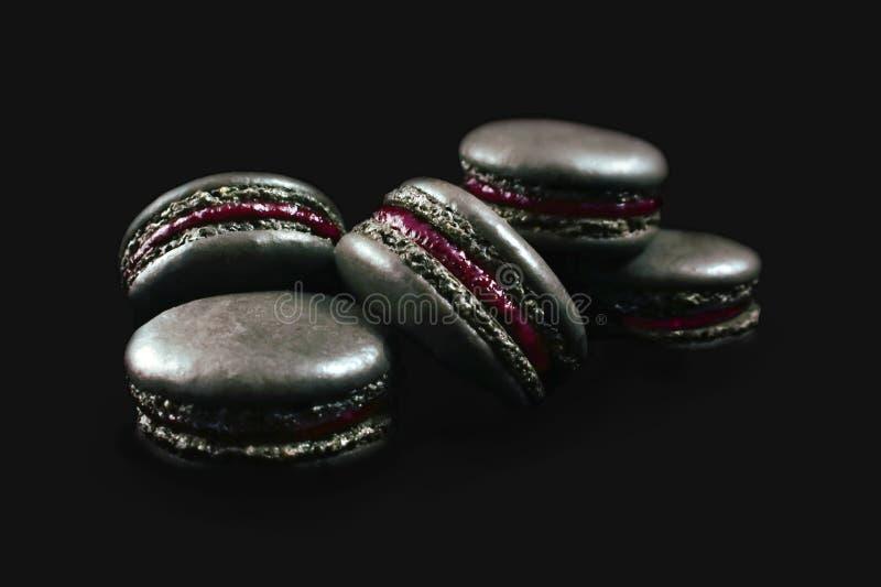 Cookies francesas pretas do macaron com escuro - enchimento vermelho isolado no fundo preto fotos de stock