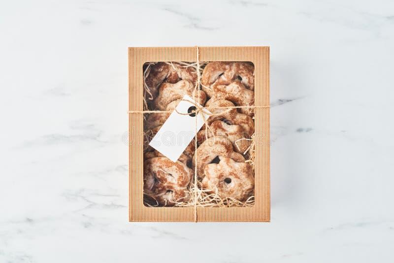 Cookies frescas do pão-de-espécie do Natal com crosta de gelo na caixa de presente de papel marrom com a etiqueta vazia do presen foto de stock