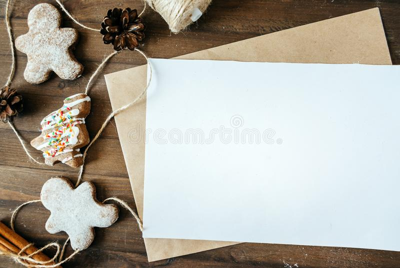 Cookies in the form of Christmas trees, gingerbread man on a brown background, a white sheet in the handle, a place for the inscri. Cookies, gingerbread man on a royalty free stock photo